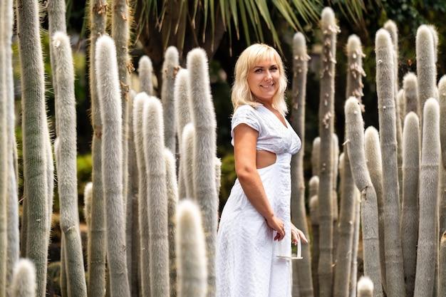 Een meisje in een witte jurk op de achtergrond van enorme cactussen op het eiland tenerife.
