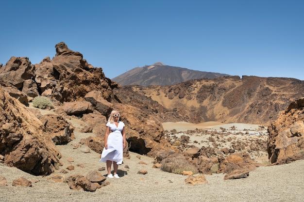 Een meisje in een witte jurk staat in de krater van de teide-vulkaan, tenerife, canarische eilanden.