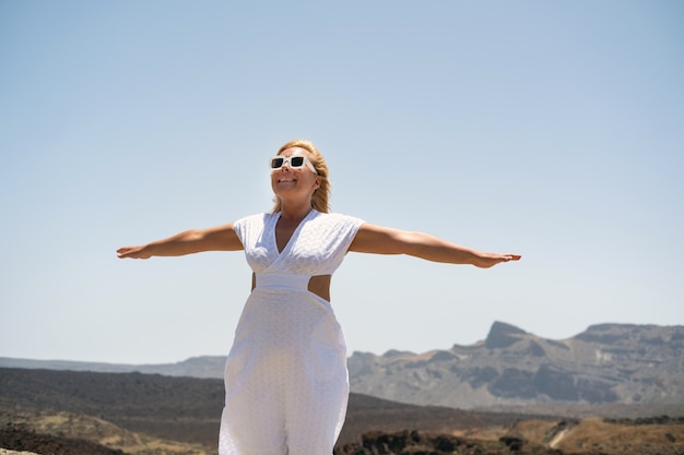 Een meisje in een witte jurk staat in de krater van de teide-vulkaan