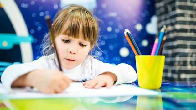 Een meisje in een witte trui tekent enthousiast met potloden