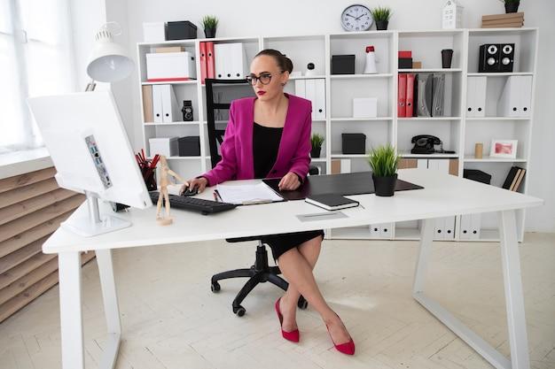 Een meisje in een zakelijke stijl werkt op een computer op kantoor