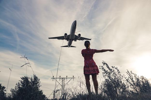 Een meisje in een zomerjurk en een vliegtuig in de lucht