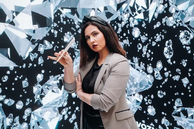 Een meisje in een zwarte broek en een jasje met een kam op een achtergrond van diamanten