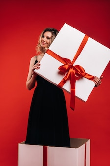 Een meisje in een zwarte jurk staat in een geschenkdoos op een rode achtergrond