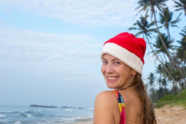 Een meisje in een zwembroek en kerstmuts op de oceaan