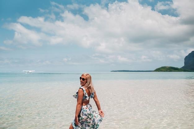 Een meisje in een zwembroek staat in de oceaan en wacht op een watervliegtuig tegen de achtergrond van de berg le morne op het eiland mauritius.