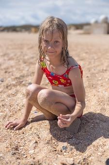 Een meisje in een zwembroek verzamelt schelpen op de zanderige kust. zomervakantie, reizen en toerisme.