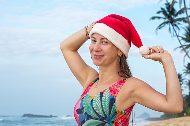 Een meisje in een zwempak en een kerstmuts op de oceaan
