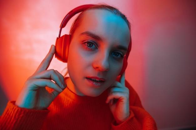 Een meisje in felgekleurde verlichting luistert naar muziek met een koptelefoon