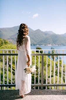 Een meisje in het lange kanten gewaad staat op een zonnige ochtend op het balkon met uitzicht op de baai van kotor