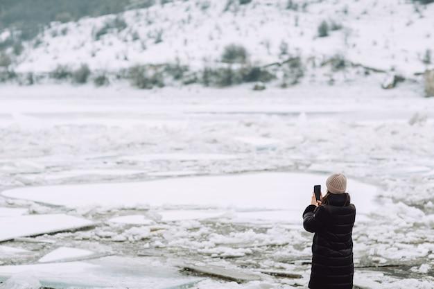 Een meisje in het zwart maakt een foto van een bevroren rivier en een besneeuwde heuvel.
