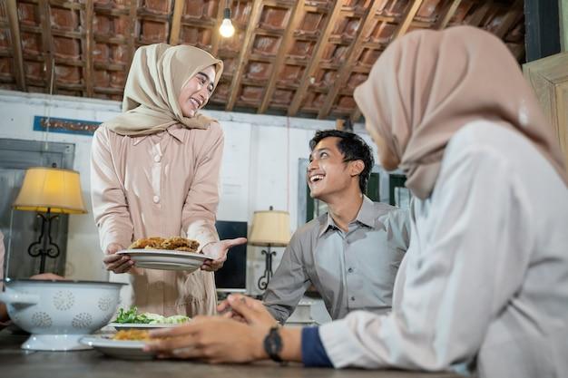 Een meisje in hijab brengt een bord gebakken kip om samen te eten tijdens het verzamelen