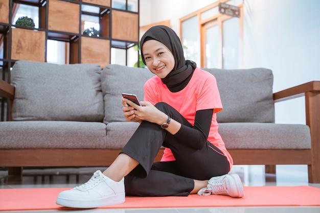 Een meisje in hijab-sportkleding glimlacht terwijl ze thuis op de vloer met een bankmuur naar een mobiel kijkt