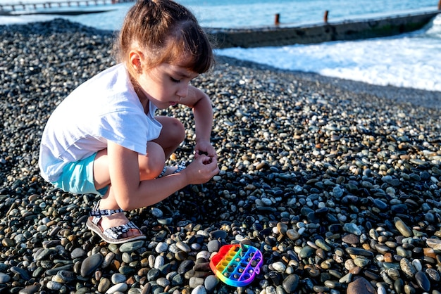 Een meisje in korte broek en t-shirt speelt met stenen aan de kust en gooit het op een vroege zomerochtend.