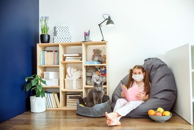Een meisje in medisch masker die op houten vloer situeren en boeken lezen tijdens quarantaine