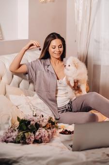Een meisje in pyjama's zit 's nachts in bed met haar witte hond die naar een laptop kijkt en snoep eet. meisje met een hond spitzer thuis in bed.
