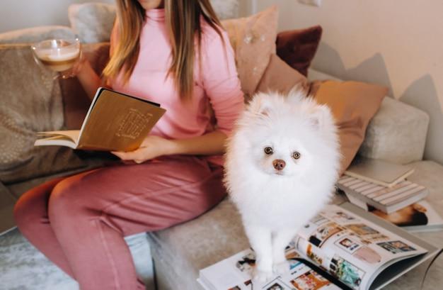 Een meisje in pyjama thuis leest een boek met haar hond spitzer, de hond en zijn baasje rusten op de bank en lezen een boek.