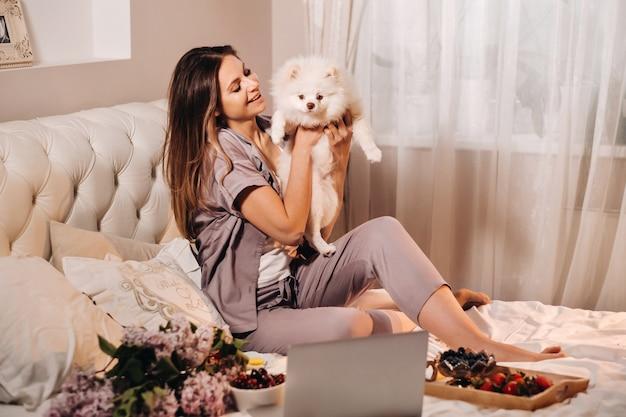 Een meisje in pyjama zit 's nachts in bed met haar witte hond die naar een laptop kijkt en snoep eet. meisje met een hond spitzer thuis in bed.