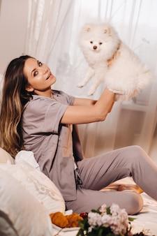 Een meisje in pyjama zit 's nachts in bed met haar witte hond kijken naar een laptop en het eten van snoep. meisje met een hond spitzer thuis in bed