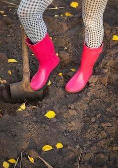Een meisje in rubberen laarzen staat in de tuin met een schop en graaft.