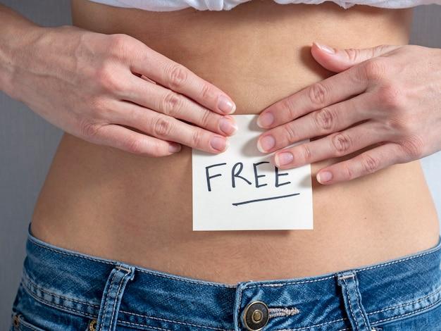 Een meisje in spijkerbroek plakt met beide handen een papieren sticker met het opschrift free op haar blote buik