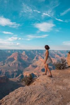Een meisje in zwart-witte jurk bij zonsondergang op het mojave point van grand canyon