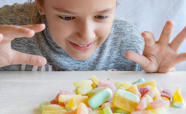 Een meisje kijkt naar een stapel snoep op tafel en wil ze van dichtbij opeten. jelly snoepjes zijn geliefd bij kinderen.