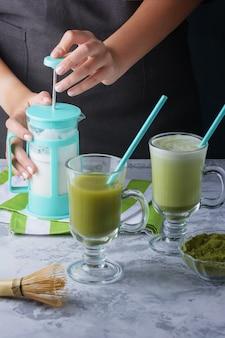 Een meisje klopt melk om een latte te maken van matcha groene thee.