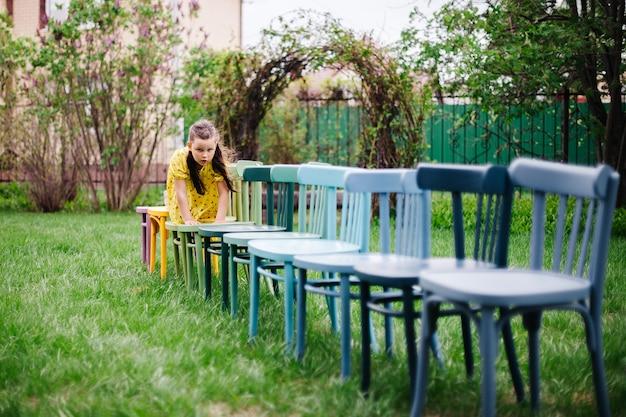 Een meisje kruipt op handen en voeten op een rij houten stoelen die een veldhuwelijk voorbereiden op een groen gazon in een ...