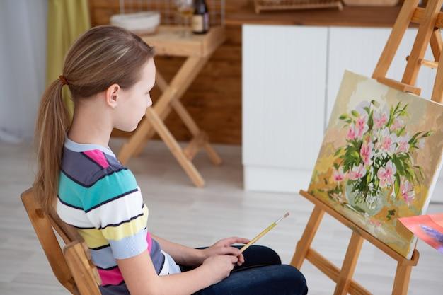 Een meisje kunstenaar schildert een foto op canvas met olieverf