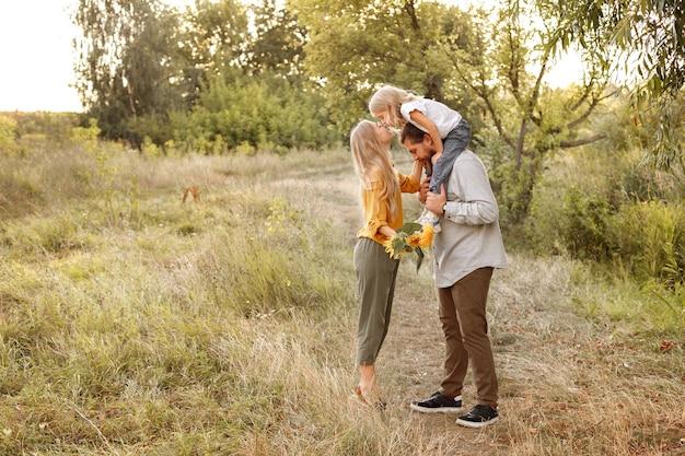 Een meisje kust haar moeder tijdens een wandeling in de natuur. gelukkig gezin
