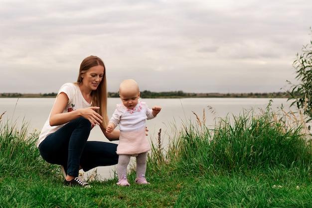 Een meisje leert met haar moeder in de natuur lopen. moeder en dochter, leren en ontwikkeling. de eerste stappen van het kind. gelukkige momenten van het leven.