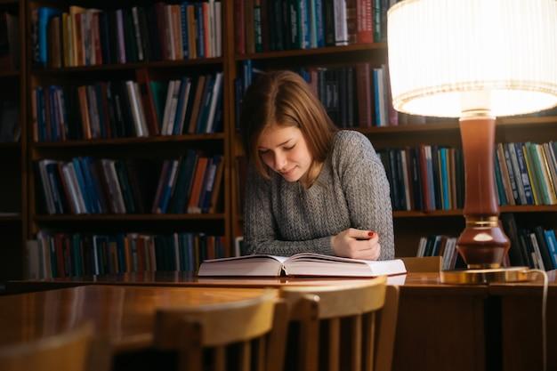 Een meisje leest een boek in een bibliotheek terwijl ze aan een tafel zit. het meisje in de bibliotheek