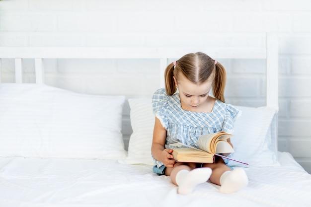Een meisje leest een boek op het bed thuis op een wit katoenen bed zittend
