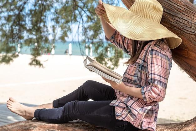 Een meisje leest een boek over een boom. de persoon abstraheerde van alles. het concept van ontspanning en rust.