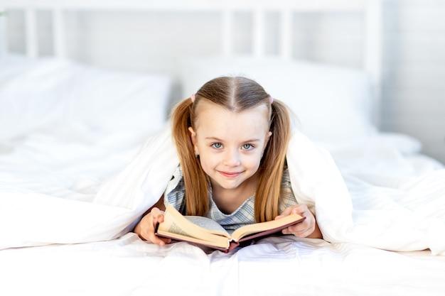 Een meisje leest thuis een boek op het bed op een wit katoenen bed onder een deken en lacht liefjes