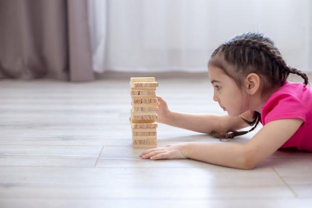 Een meisje ligt op de grond in de kamer en speelt het spel van torenhouten blokken. gezinsbordspellen