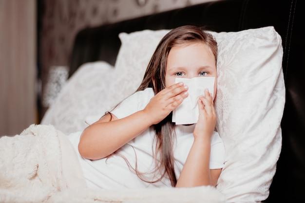 Een meisje ligt op het bed in een mooie slaapkamer, niest en bedekt haar neus met een zakdoek, het koude herfstseizoen, de tweede golf van het virus