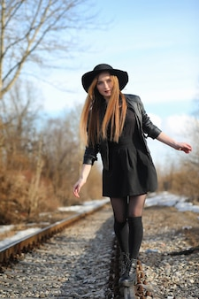 Een meisje loopt door de stadsstraat in een leren vest met een telefoon. jong mooi meisje in een hoed en met een donkere make-up buiten. meisje in de gotische stijl op straat.