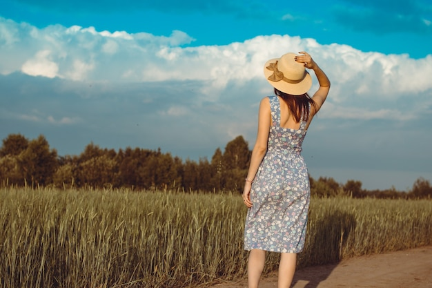 Een meisje loopt in de zomer in een veld waar rogge of tarwe groeit. ze heeft een hoed in haar handen. 6