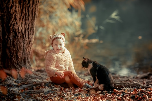 Een meisje loopt in het najaar buiten op een openbaar park en naast haar een zwarte kat