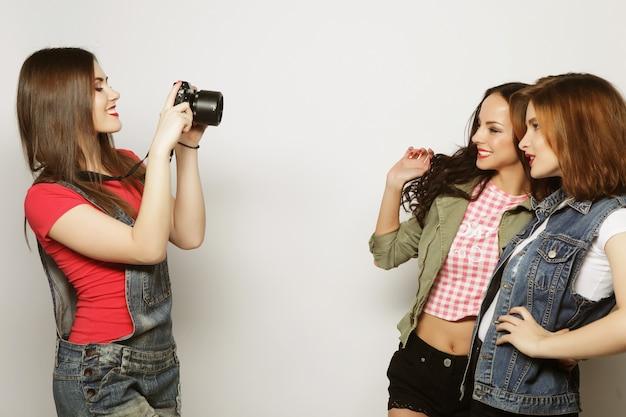 Een meisje maakt een foto van haar vrienden. concept van vriendschap en plezier. beste vrienden genieten van het moment met moderne camera.