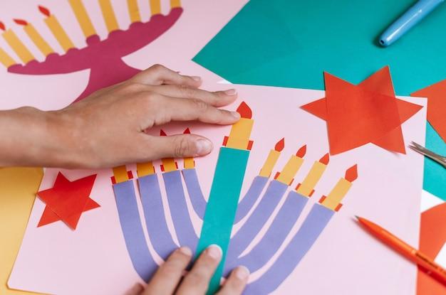 Een meisje maakt een kaart voor gelukkige chanoeka met haar handen, een kandelaar en kaarsen op de kaart