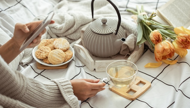 Een meisje maakt foto's op de telefoon van een lentesamenstelling met thee, koekjes en tulpen in bed