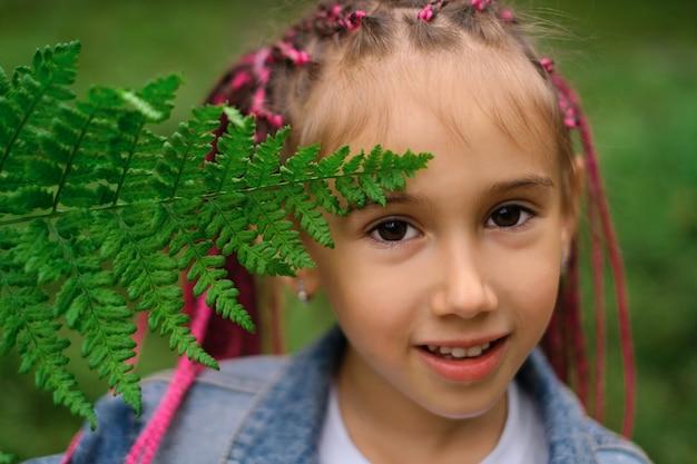 Een meisje met afrikaanse staartjes op een groene achtergrond bedekt haar gezicht met een varenblad