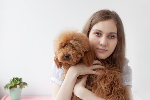 Een meisje met blauwe ogen en bruin haar houdt een roodbruine miniatuur ruige poedel in haar armen en omhelst haar