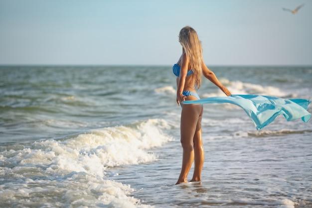 Een meisje met blond haar in een blauwachtig zwempak en een heldere sjaal loopt langs het strand