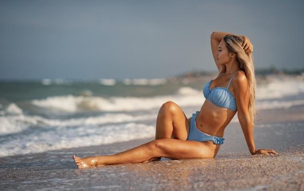 Een meisje met blond haar in een delicaat zwempak zit aan zee en geniet van de plons van de golven