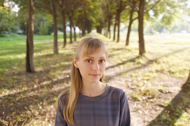 Een meisje met blond haar, in een gestreepte jurk, op een zomerse dag. een jonge vrouw met een kalme blik, kijkend naar de camera