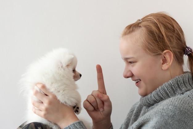 Een meisje met blond haar in een grijze trui, glimlachend, met een witte, pluizige pommerse puppy in haar armen en schudt haar wijsvinger naar de puppy.